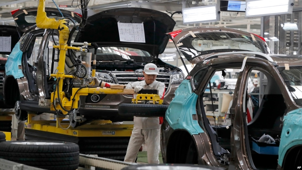 FILE - A worker prepares to put a spare tire into a Haval SUV H2 model