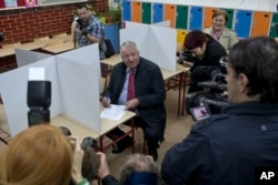 Vojislav Seselj, center, a Serb ultra-nationalist politician, talks to members of the media before casting his ballot at a polling station in Belgrade, Serbia, Sunday, April 24, 2016.