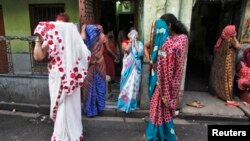 Indian sex workers cover their faces at the Sonagachi red-light area in Kolkata July 24, 2012.
