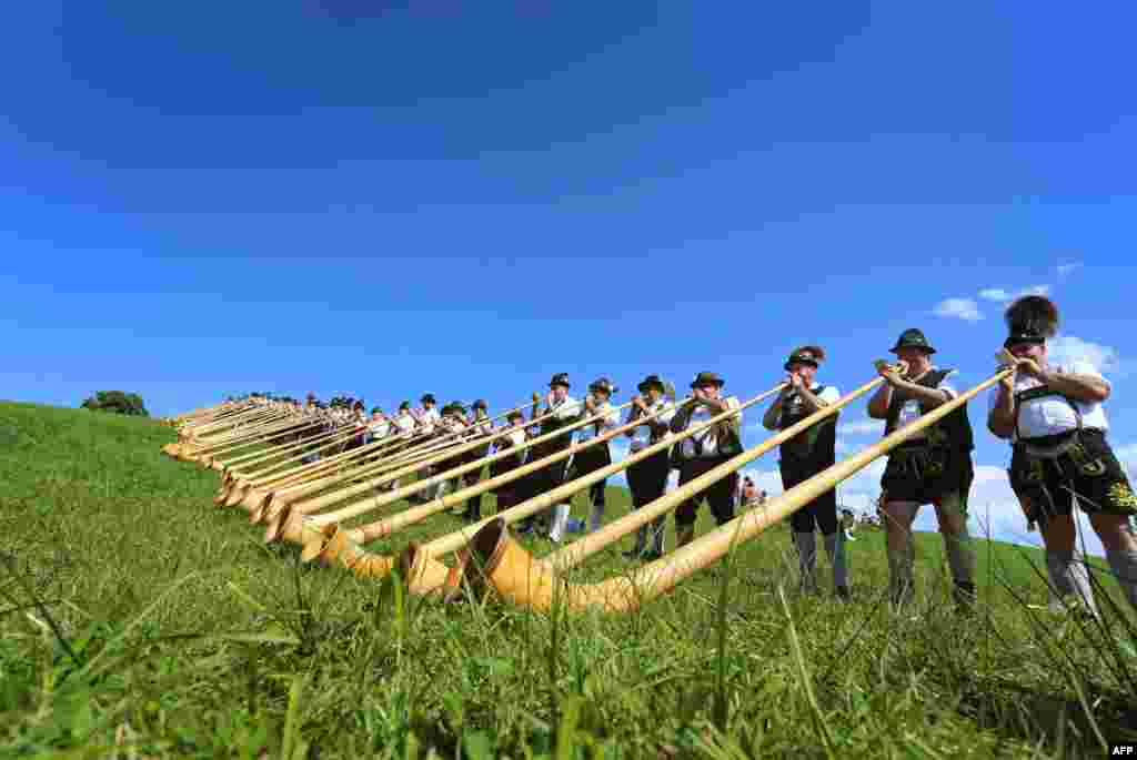 Alphorn players take part during a mass performance of 300 alphorn blowers in Nesselwang, southern Germany.