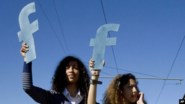 "Protesters hold ""f""s in recognition of social network site Facebook's role in the North African revolts, during a protest in Rabat, Morocco (Mar 2011 file photo)"