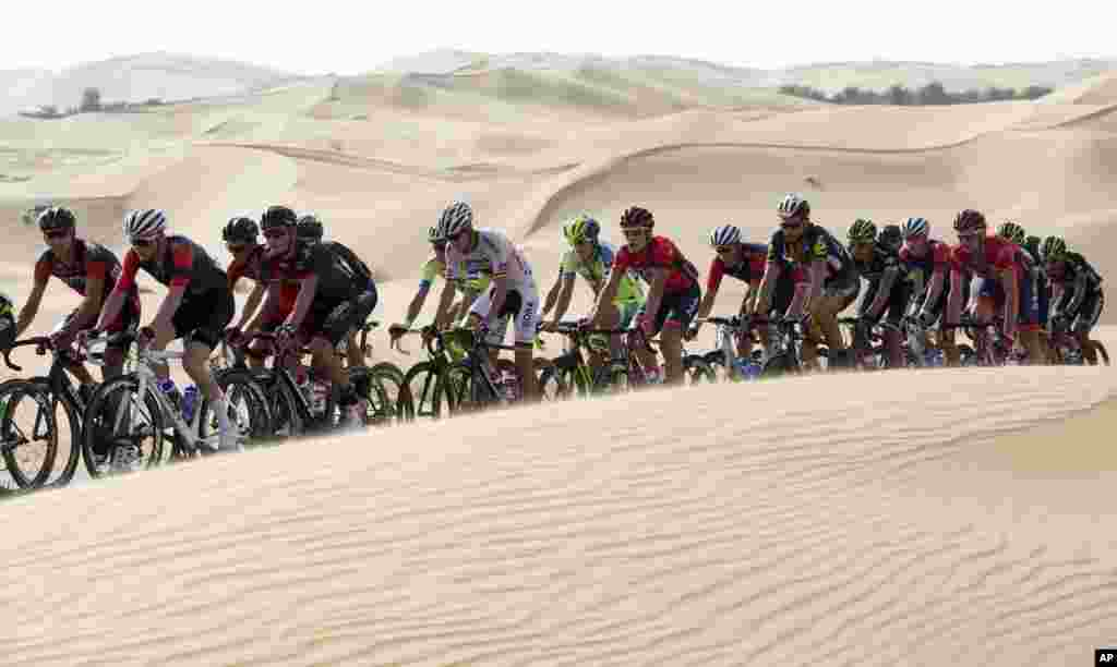 The pack pedals along desert dunes, during the first stage of the Abu Dhabi tour cycling race, from Qasr Al Sarab to Madinat Zayed, UAE.