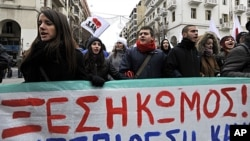 Protesters carry a banner which reads in Greek '' uprising '' during a protest against austerity measures in the northern port city of Thessaloniki, Greece, February 11, 2012.