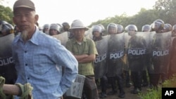 Villagers stand next to riot police deployed to Vietnam's northern Hung Yen province during a protest on April 24, 2012. (AP file photo)