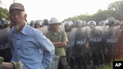 Villagers stand next to riot police deployed to Vietnam's northern Hung Yen province during a protest on April 24, 2012. Local residents tried block police from taking control of a disputed plot of land outside Hanoi in the second high-profile clash over