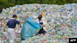 This photo taken on July 16, 2018 shows volunteers sorting out plastic bottles at a recycling centre run by a non-profit Buddhist organisation in Taipei. Taiwan started recycling plastic more than a decade ago and today it boasts more than 70 percent recy