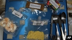 FILE - A tray similar to those used in space flight displays a sample of foods available to astronauts.