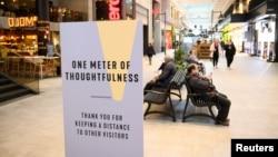 Një tabelë inkurajon distancimin fizik në një qendër tregtare në Stokholm