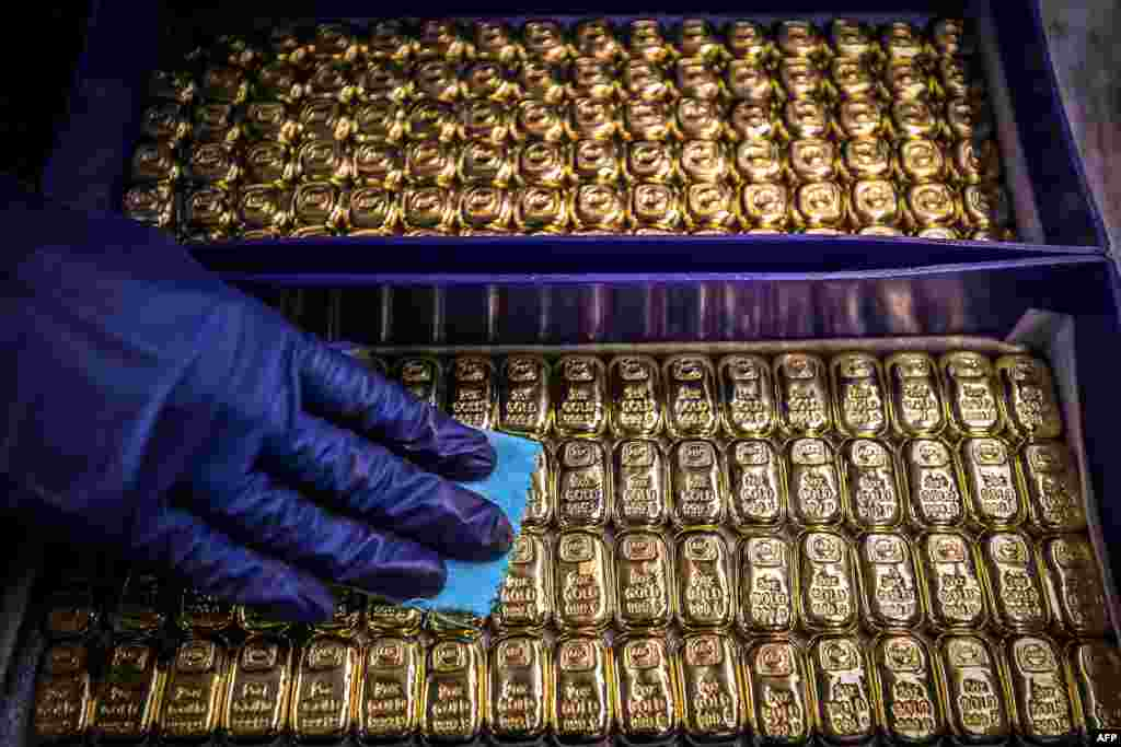 A worker polishes gold bullion bars at the ABC Refinery in Sydney, Australia. Gold prices hit $2,000 an ounce on markets for the first time, the latest surge in a commodity.