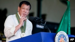 FILE - Philippine President Rodrigo Duterte gestures while addressing army troops during the 120th anniversary celebration of the Philippine Army, April 4, 2017, at Fort Bonifacio.