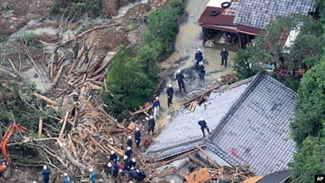 An aerial view of rescue workers searching for missing people among the debris of houses destroyed in Tanabe, Wakayama Prefecture, September 5, 2011.