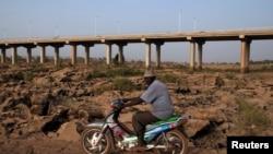 Un homme conduisant sa moto, Bamako, 26 février 2014