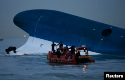 FILE - Maritime police search for missing passengers in front of the South Korean ferry Sewol, which sank at the sea off Jindo April 16, 2014.