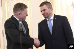 FILE - Outgoing Slovakian Prime Minister Robert Fico, left, shakes hands with Peter Pellegrini, who will replace Fico as prime minister, at the Presidential palace in Bratislava, March 15, 2018.