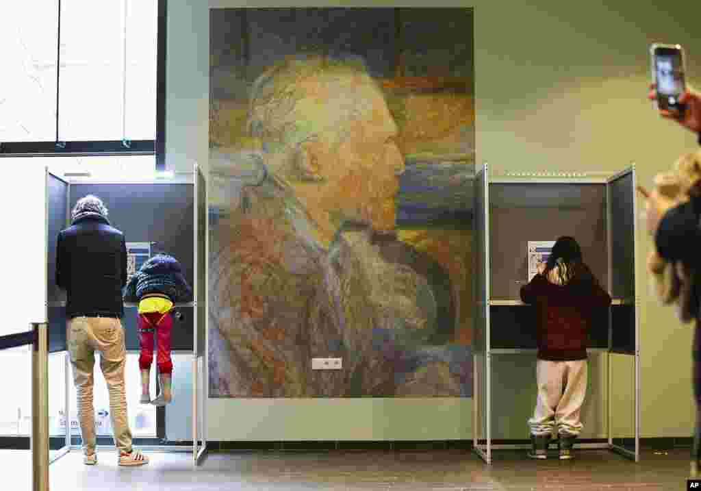 A mother uses her mobile phone to take a picture of her husband and child in a voting booth, left, prior to casting their ballot for a general election at the Van Gogh Museum in Amsterdam, Netherlands.