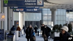 FILE - Passengers walk through Terminal 3 at O'Hare International Airport in Chicago, Thursday, Jan. 31, 2019.