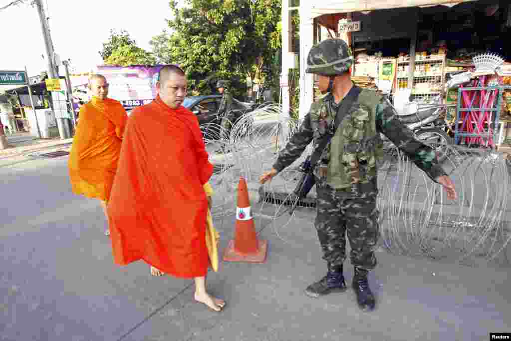 "Barefoot Buddhist monks walk past a checkpoint near a pro-government ""red shirt"" supporter encampment in Nakhon Pathom province, on the outskirts of Bangkok, May 22, 2014."