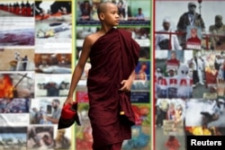 FILE - A Buddhist monk walks past anti-Muslim billboards inside the Masoeyein Monastery complex in Mandalay, Myanmar, Oct. 7, 2015.