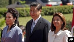 China's President Xi Jinping, center, and his wife Peng Liyuan, left, stand alongside Costa Rica's President Laura Chinchilla as they listen to their national anthems at a welcoming ceremony at the presidential house in San Jose, Costa Rica, June 3, 2013.