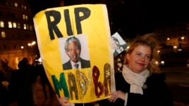 A woman with a banner pays tribute to Nelson Mandela outside the South African High Commission in London, Dec. 6, 2013.
