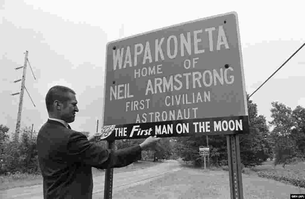 С не меньшим торжеством Армстронга чествовали на родине астронавта – в городке Вапаконета, штат Огайо. На тот момент в нем проживало не больше семи тысяч человек, и тот факт, что уроженец города стал первым человеком на Луне, мгновенно сделал Армстронга главной достопримечательностью этих мест.  Хотя в Вапаконете Армстронг провел значительную часть своего детства, городок был не единственным местом жительства его семьи. Из-за специфики работы отца семья Армстронга часто переезжала, сменив в общей сложности 16 мест проживания внутри штата Огайо.  На снимке – Чарльз Брэдинг, друг Нила Армстронга, примеряет образец памятной таблички к знаку на въезде в город. Надпись на знаке: «Вапаконета – родина первого гражданского астронавта и первого человека на Луне».