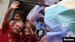 FILE - Brazil's President and Workers' Party (PT) presidential candidate Dilma Rousseff (R) and her predecessor Luiz Inacio Lula da Silva wave to supporters during a campaign rally in Sao Paulo, Oct. 3, 2014.