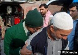 Um estudante chora no ombro de um homem, após ter sido salvo pelo exército paquistanês. Peshawar, Dez. 16, 2014.