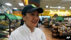 In this April 3, 2018, photo, mountain climber Lhakpa Sherpa prepares to start her shift as a dishwasher at the Whole Foods Market in West Hartford, Conn. (AP Photo/Pat Eaton-Robb)