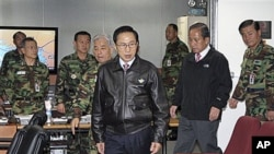 South Korean President Lee Myung-bak, center, arrives with Defense Minister Kim Tae-young, second right, in Seoul, South Korea, as the military was put on top alert after North Korea's artillery attack on the South Korean island of Yeonpyeong.