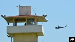 FILE - A police helicopter flies over the state prison in Acapulco, Mexico, July 6, 2017.