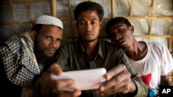 Rohingya Muslim refugee Mohammad Karim, 26, center, shows a mobile video of Gu Dar Pyin's massacre to other refugees in Kutupalong refugee camp, Bangladesh, Jan. 14, 2018.