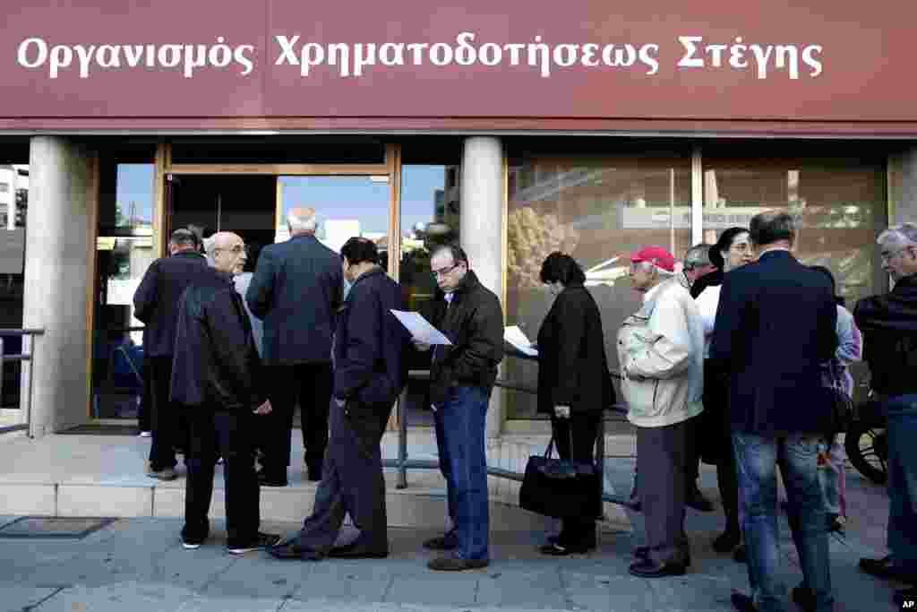 People line up outside a branch of Cyprus' Housing Finance Corporation, a state-run bank that mainly helps low and middle income people, in capital Nicosia, March 29, 2013.