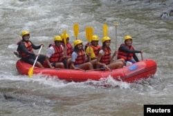 FILE - Former United States President Barack Obama (2nd left), his wife Michelle (3rd left) and with his daughters Sasha (center) and Malia (2nd right) go rafting while on holiday in Bongkasa Village, Badung Regency, Bali, Indonesia, June 26, 2017.