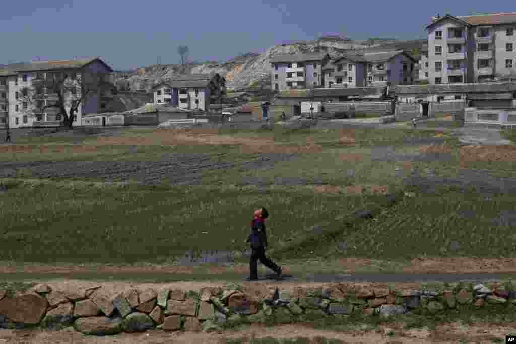 A North Korean boy walks along a path in front of a village on a road south of Kaesong, North Korea, north of the demilitarized zone which separates the two Koreas, April 24, 2013.