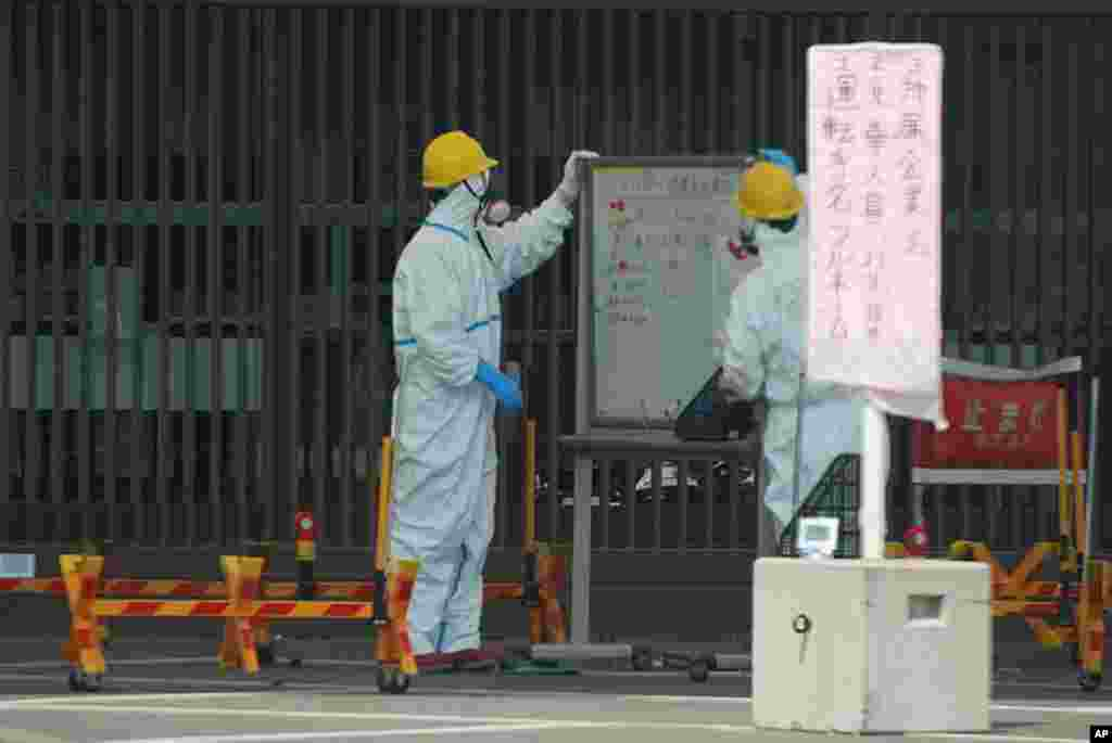 Guards read a whiteboard near the Fukushima-1 nuclear plant's main gate, April 13, 2011 (VOA Photo S. Herman)