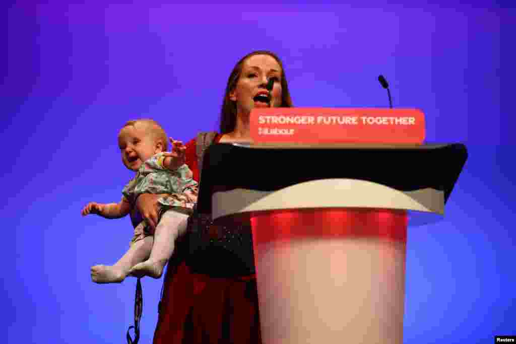 Delegate Catherine Atkinson speaks as she carries her 9-month-old Elena, during Britain's Labor Party annual conference in Brighton, Britain.