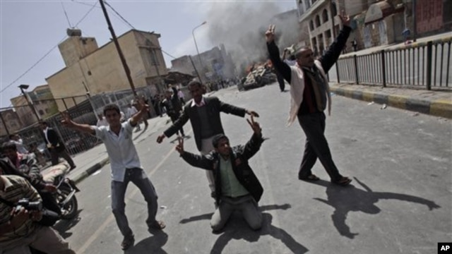Yemeni anti-government demonstrators celebrate after setting on fire a vehicle belonging to supporters of President Ali Abdullah Saleh during clashes in Sana'a, Yemen, February 22, 2011