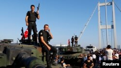 FILE - Policemen stand atop military armored vehicles after troops involved in the coup surrendered on the Bosphorus Bridge in Istanbul, Turkey, July 16, 2016.