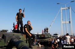 FILE - Policemen stand atop military armored vehicles after troops involved in the coup surrendered on the Bosphorus Bridge in Istanbul, July 16, 2016.