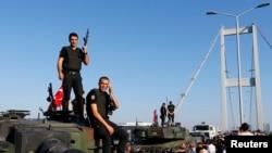 Polislər təslim olmuş hərbçilərdən ələ keçirdikləri zirehli maşının üzərində dayanıblar. Bosfor Körpüsü, İstanbul. 16 iyul, 2016.
