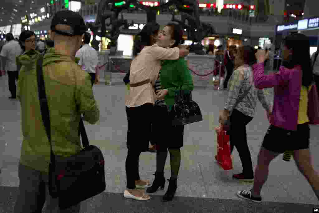 Guzulnur, wife of detained Uighur scholar Ilham Tohti bids farewell to friends before leaving on a flight for Urumqi at the capital airport in Beijing, China, Sept. 15, 2014.
