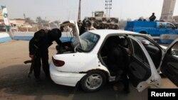 Cảnh sát lục soát một chiếc xe tại một chốt kiểm soát sau ở Abu Ghraib.