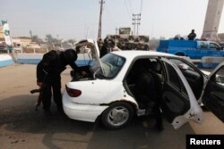 FILE - Police officers search a vehicle at a checkpoint, as security increases after a bomb attack, at Abu Ghraib district, west of Baghdad, Iraq, Jan. 9, 2014.