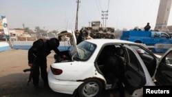 Polis işçiləri Əbu Qreybdə avtomobilləri yoxlayır