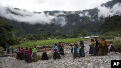 After attending a church service, women and children walk to a communal meeting to try and solve problems associated with housing and donations received by the international community, in the makeshift settlement Nuevo Queja, Guatemala, Sunday, July 11, 2