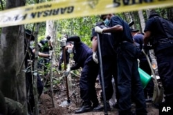A Malaysian police forensic team excavates an unmarked grave in Wang Burma at the Malaysia-Thailand border outside Wang Kelian, Malaysia on Tuesday, May 26, 2015. (AP Photo)