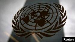 Tòa nhà trụ sở chính của Liên Hiệp Quốc được chụp ảnh qua một cửa sổ với logo ở phía trước.