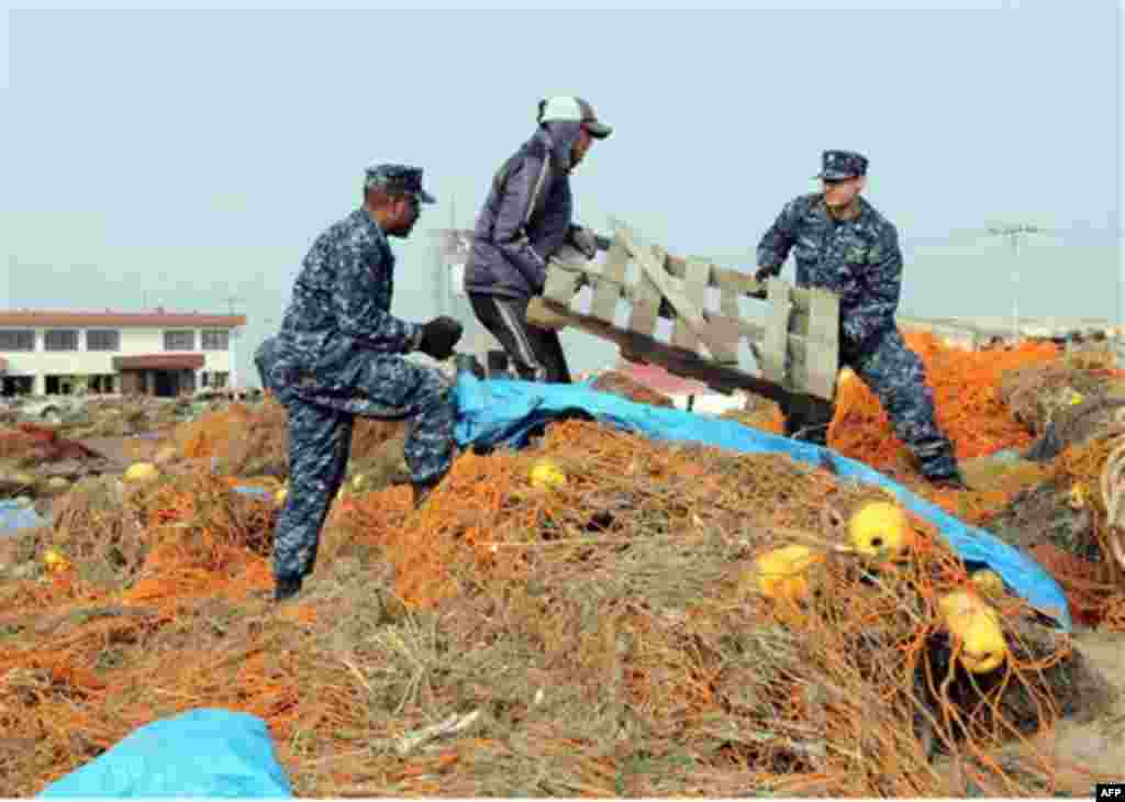 In a March 14, 2011 photo provided by the Navy Visual News Service, Navy Aerographer�s Mate 2nd Class John Dicola from New York, and Intelligence Specialist 1st Class Shakir Briggs from Orlando, Fla., helpa local civilian remove debris from the Misawa Fis