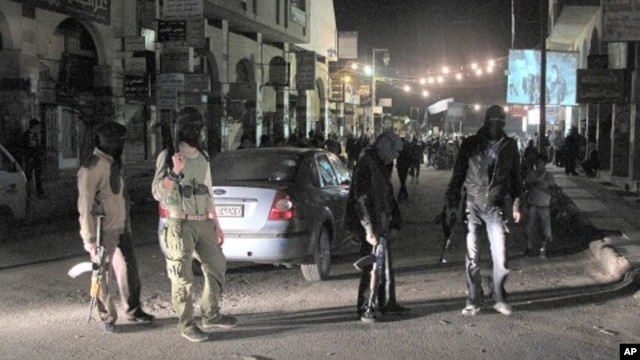 Free Syrian Army fighters guard a night protest in a neighborhood in Damascus, Syria, April 4, 2012.