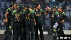 Pakistan's fielders congratulate Shahid Afridi as he dismissed Australia's Glenn Maxwell successfully during their match of the ICC Twenty20 World Cup at the Sher-E-Bangla National Cricket Stadium in Dhaka March 23, 2014. REUTERS/Andrew Biraj (BANGLADESH